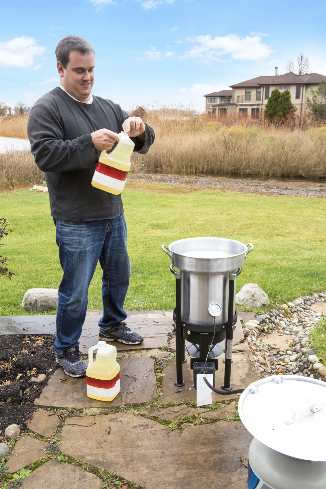 A man is getting ready to pour oil in outdoor deep fryer in preparation for deep frying his Thanksgiving turkey. Deep fried turkey is delicious but there is a danger of explosion or fire which is why it is always cooked outside. Shot with a Canon 5D Mark 3. rm
