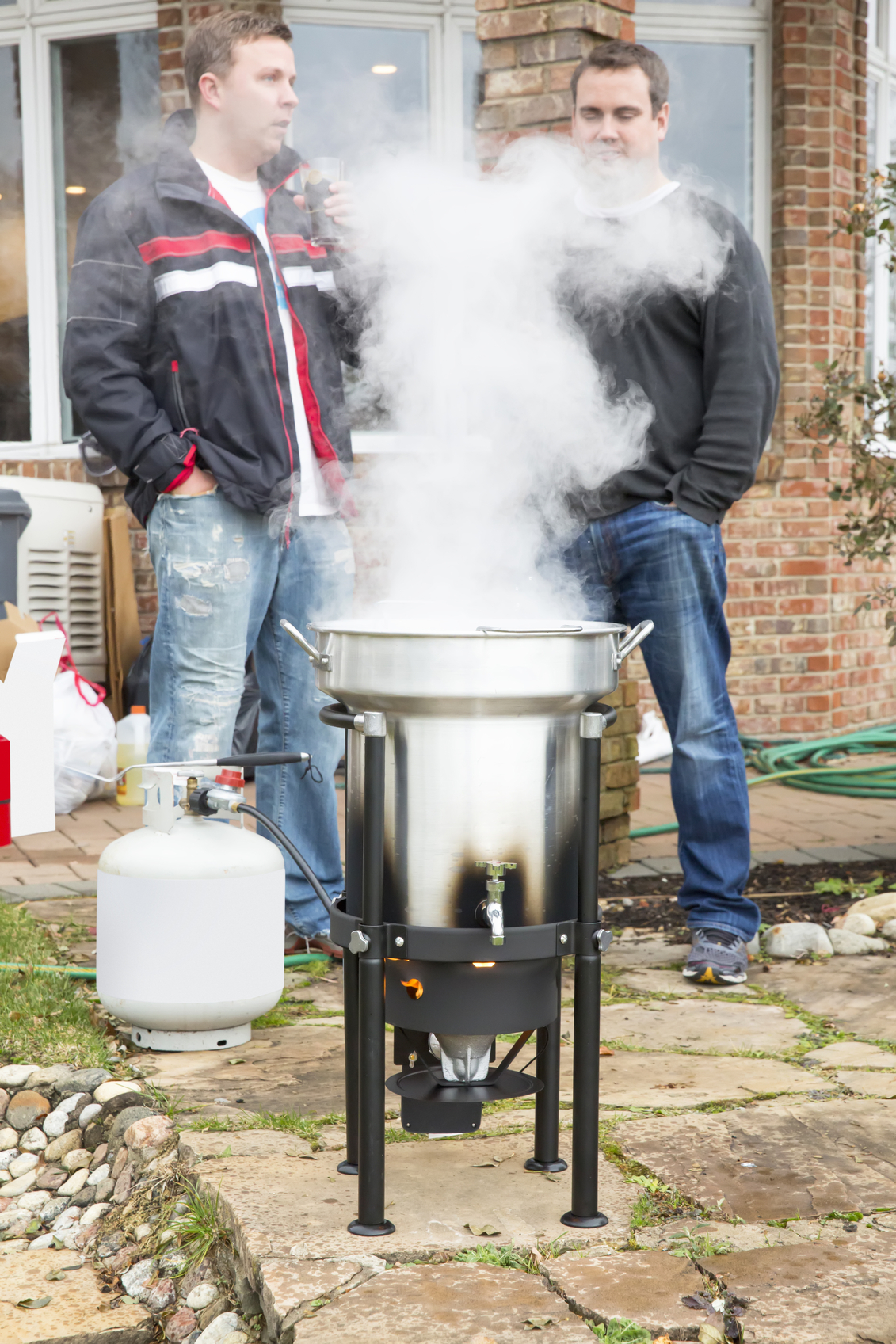 Two caucasian men are standing in a backyard with a stainless deep fryer that is cooking their Thanksgiving turkey. Steam is coming out of the pot because the oil is extremely hot. There is a propane tank attached to the deep fryer. Shot with a Canon 5D Mark 3. rm