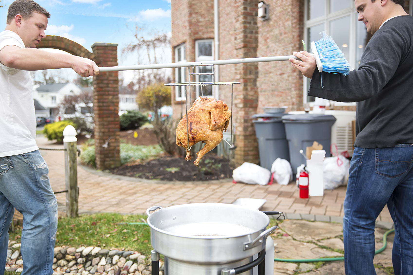 Two caucasian men are using a broom to carry a deep fried turkey they have just lifted out of the hot oil in a deep fryer into the house. The fryer is outside because it is too dangerous to have it indoors. Taken with a Canon 5D Mark 3. rm
